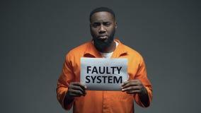 Prisioneiro masculino afro-americano que guarda a pilha defeituosa do sinal do sistema dentro, direitos humanos filme
