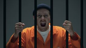 Prisioneiro masculino perigoso agressivo com a cicatriz na cara que guarda barras e gritaria video estoque