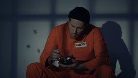Prisioneiro masculino que come o papa de aveia na pilha, insuficiente nutrição, circunstâncias pobres filme