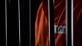 Prisioneiro na posição uniforme alaranjada atrás das barras, punição para o crime cometido fotos de stock