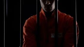 Prisioneiro na posição uniforme alaranjada atrás das barras, punição para o crime cometido fotos de stock royalty free