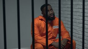 Prisioneiro preto desesperado que senta-se na pilha, pessoa errada acusada, sistema defeituoso video estoque