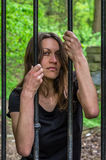 Prisioneiro 'sexy' bonito novo da menina atrás de uma cerca do ferro imagens de stock