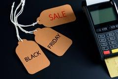 Prislapp- och kreditkortmaskin på svart tabellbakgrund, Black Friday begrepp Royaltyfri Fotografi