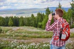 Prismáticos de observación del viajero masculino en la distancia contra un bosque y un cielo nublado imagen de archivo