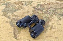 Prismáticos en mapa del mundo Imagen de archivo libre de regalías