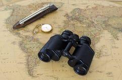 Prismáticos en mapa del mundo Foto de archivo libre de regalías