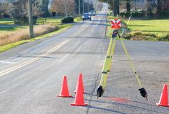 Surveyor`s Prism and Tripod on Street. A prism attached on a tripod is being used as a target for measuring distance by professional surveyors collecting date stock photos