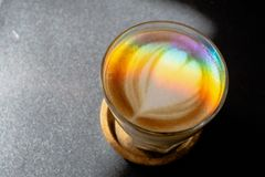 A prism dispersing sunlight splitting into a spectrum on coffee cup with heart shape latte art foam on black table. stock photo