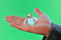 Prism on the palm. Man holds in the palm of a glass prism against a green background royalty free stock photos