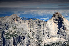 Prisojnik, Razor and cloud layers, Julian Alps. Peaks of Prisojnik, or Prisank, left and Razor right, in the background Dobratsch with radio tower, Gailtal Alps Stock Image