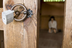 Prison. A person sitting in a prison cell, padlock focused royalty free stock images