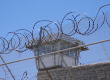 Prison. Barbed fence and guard tower behind