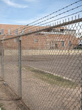 Prison barb wire wall and prison building. Prison barb wire wall fence and prison building Royalty Free Stock Photo