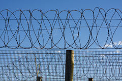 Prison Barbed Wire. Coils of barbed wire on top of a fence provide security at a penitentiary in South Africa. The barb wire is symbolic of protection and Stock Image