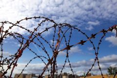 Prison. Barbed wire. Barbed wire on blue sky background with white clouds. Wire boom. Military conflict . Syria. Barbed wire. Barbed wire on blue sky background Stock Image