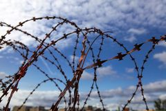 Prison. Barbed wire. Barbed wire on blue sky background with white clouds. Wire boom. Military conflict . Syria. Barbed wire. Barbed wire on blue sky background Stock Photos
