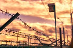 Barbed wire on a background of clouds and crimson sunset, with views of the birdhouse. Prison barbed wire fence enclosing the prison on the background of storm Royalty Free Stock Image