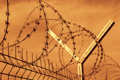 Prison barbed wire fence at sunset.  Stock Photography