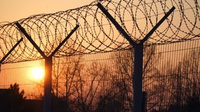 Prison barbed wire fence at sunset. Bright sun and trees silhouette freedom 4k. Prison barbwire fence at sunset. Bright sun and trees silhouette freedom 4k stock video