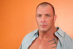Prison Break. Handsome muscular man with tattoos and open shirt stock images