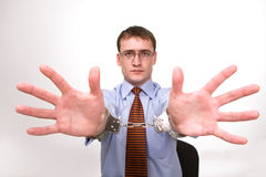 Prison break. Handsome young businessman bound to laptop with handcuffs Royalty Free Stock Photos