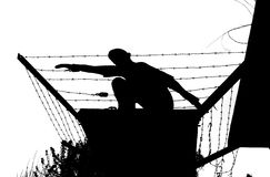 Prison breakout. Silhouette of a fleeing man over barbed wire royalty free stock images
