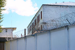 Prison building. Behind the wall with barbed wire stock photos