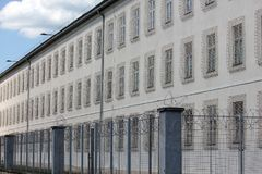 Prison building with razor wire fence. And cloudy blue sky royalty free stock photos