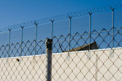Prison camp Razor Wire. Picture taken from the outside of a prison camp, showing a razor wire at the top Royalty Free Stock Photo