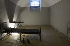 Prison cell. Old prison cell in which a bed, table, lamp, window Stock Photography