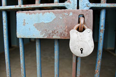 Prison Cell Padlock. Padlock on the cell door of a prison. Focus on the padlock with copy space room on the latch. Dark and gloomy bars and cell in background stock photography