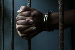Prison. Close up prisoner holding bar in jail Stock Image