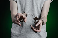 Prison and convicted topic: man with handcuffs on his hands in a gray T-shirt and blue jeans on a dark green background in the stu Stock Photo