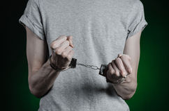 Prison and convicted topic: man with handcuffs on his hands in a gray T-shirt and blue jeans on a dark green background in the stu Royalty Free Stock Photos
