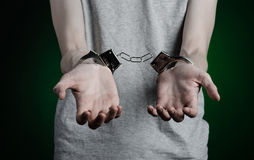 Prison and convicted topic: man with handcuffs on his hands in a gray T-shirt and blue jeans on a dark green background in the stu Stock Images