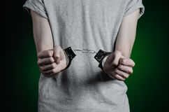 Prison and convicted topic: man with handcuffs on his hands in a gray T-shirt and blue jeans on a dark green background in the stu Stock Image