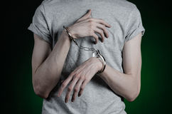 Prison and convicted topic: man with handcuffs on his hands in a gray T-shirt and blue jeans on a dark green background in the stu Royalty Free Stock Photography