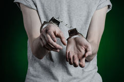 Prison and convicted topic: man with handcuffs on his hands in a gray T-shirt and blue jeans on a dark green background in the stu Stock Photos