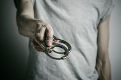 Prison and convicted topic: man with handcuffs on his hands in a gray T-shirt on a gray background in the studio, put handcuffs on Stock Photo