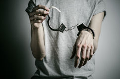 Prison and convicted topic: man with handcuffs on his hands in a gray T-shirt on a gray background in the studio, put handcuffs on Royalty Free Stock Photos