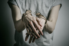Prison and convicted topic: man with handcuffs on his hands in a gray T-shirt on a gray background in the studio, put handcuffs on Royalty Free Stock Photography