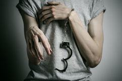 Prison and convicted topic: man with handcuffs on his hands in a gray T-shirt on a gray background in the studio, put handcuffs on. Prison and convicted topic Stock Photos
