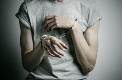Prison and convicted topic: man with handcuffs on his hands in a gray T-shirt on a gray background in the studio, put handcuffs on. Prison and convicted topic Stock Images