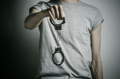 Prison and convicted topic: man with handcuffs on his hands in a gray T-shirt on a gray background in the studio, put handcuffs on Stock Image