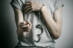 Prison and convicted topic: man with handcuffs on his hands in a gray T-shirt on a gray background in the studio, put handcuffs on. Prison and convicted topic Royalty Free Stock Photo
