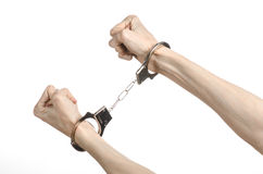 Prison and convicted topic: man hands with handcuffs isolated on white background in studio, put handcuffs on killer Stock Images