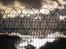 Prison fence with barbed wire. On the cloudy sky background Stock Photography