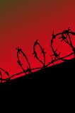 Prison fence silhouette on red gradient sky Royalty Free Stock Images