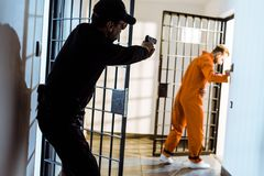 Prison guard aiming gun at escaping. Prisoner royalty free stock images